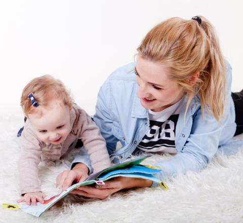 Image of mother and baby girl reading on a white carpet.