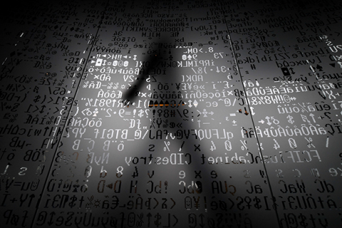 image of shadowy figure over computer code
