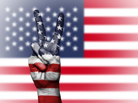 USA flag and hands making a peace sign