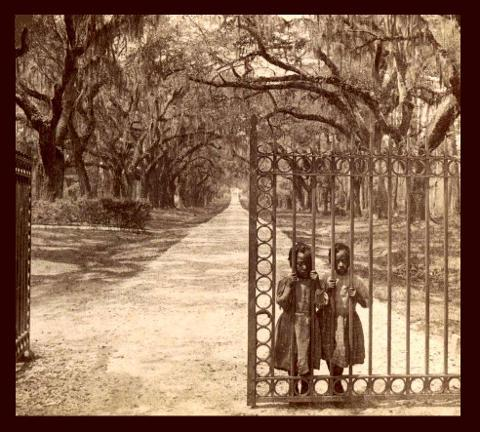 Two young African American girls standing behind the bars of a gate.
